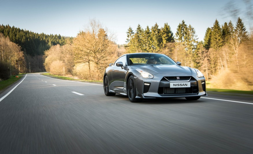 Grey 2017 Nissan GT-R driving on road with trees in background