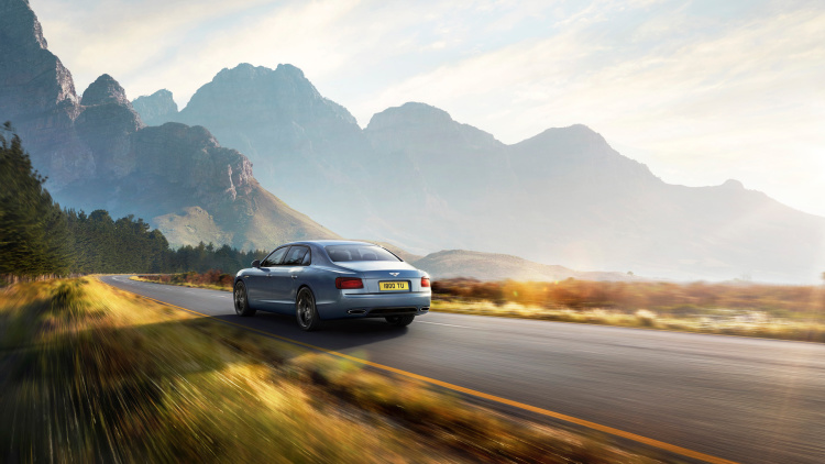 Bentley Flying Spur W12 S driving along road with mountains in the background